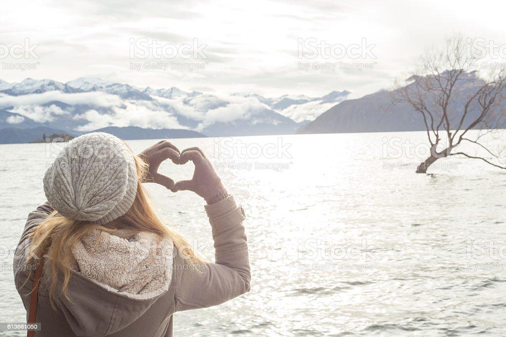 Young woman makes heart shape finger frame on lake Wanaka stock photo