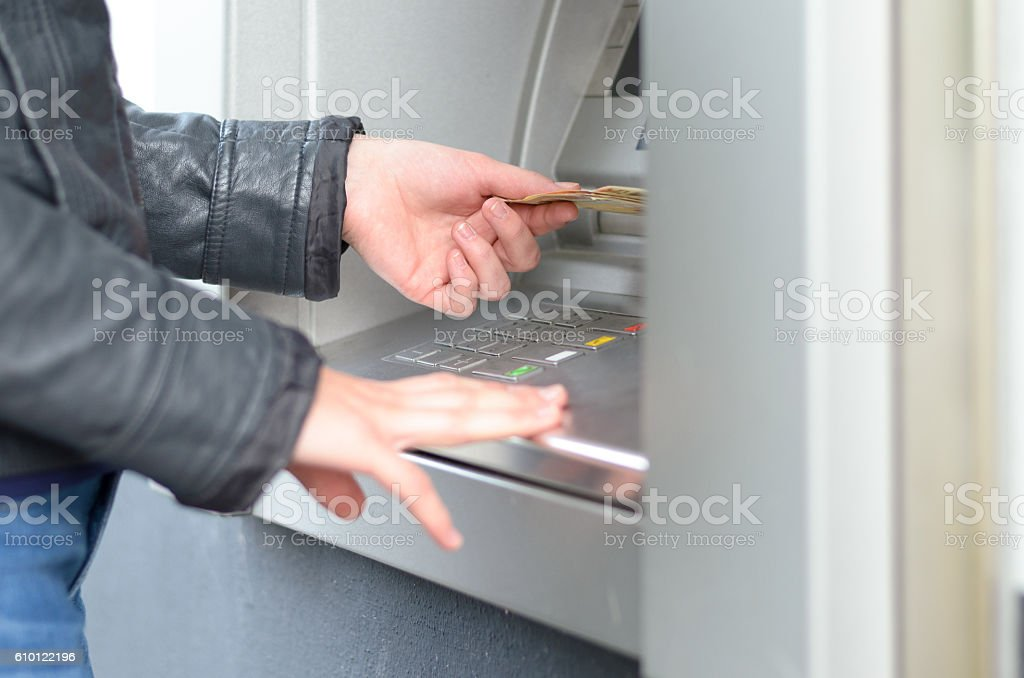 Young woman making a banking withdrawal stock photo