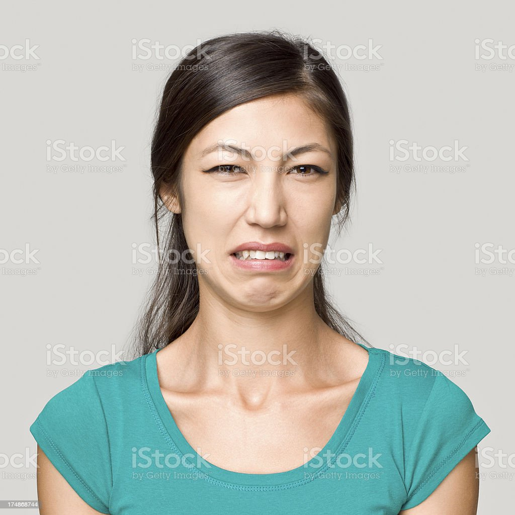 Young woman making a disgusting face expression stock photo