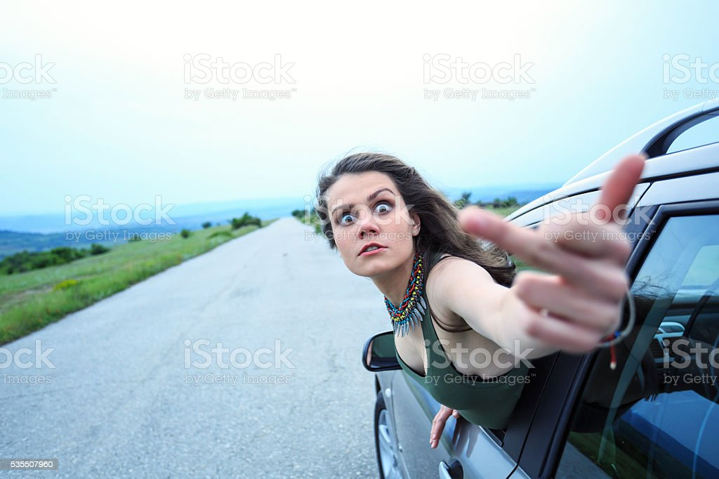 Young woman making abusive gesture on the road stock photo