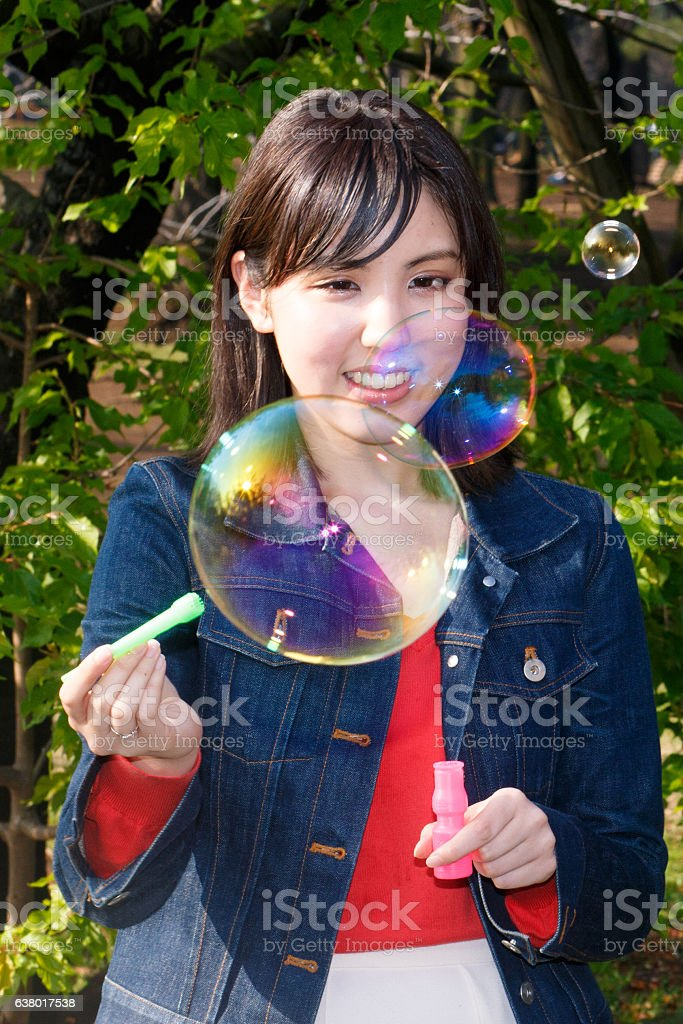 Young woman making big soap bubbles stock photo