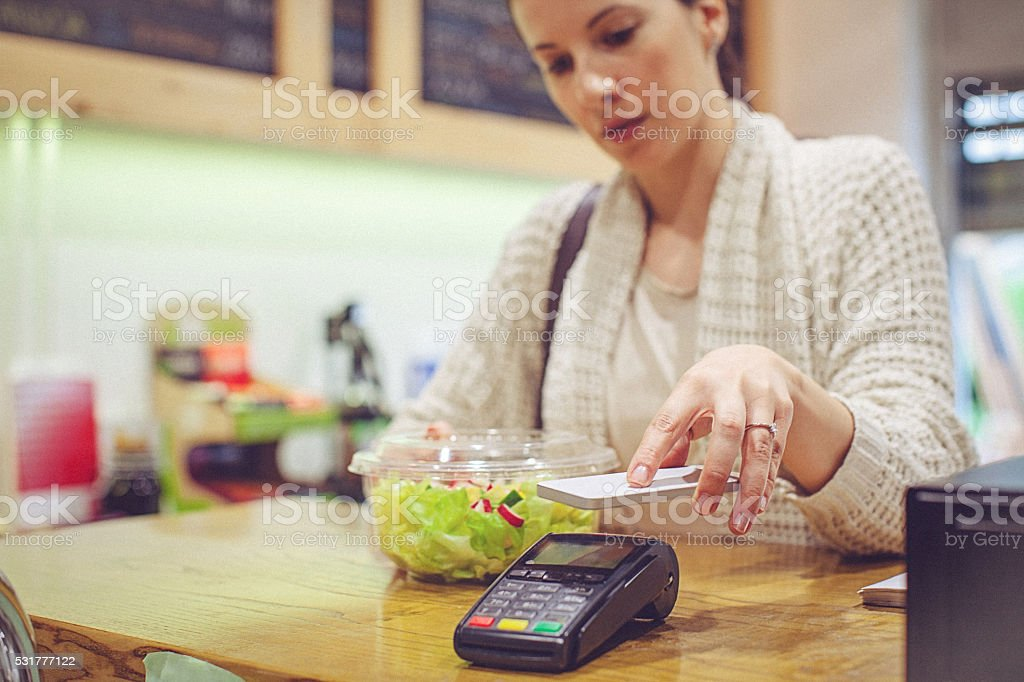 Young woman making contactless payment with smartphone stock photo