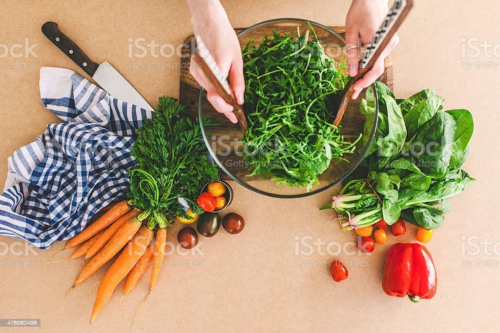 Young woman making fresh salad stock photo