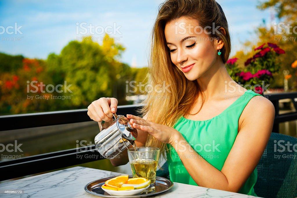 Young Woman Making Green Tea Outdoors stock photo