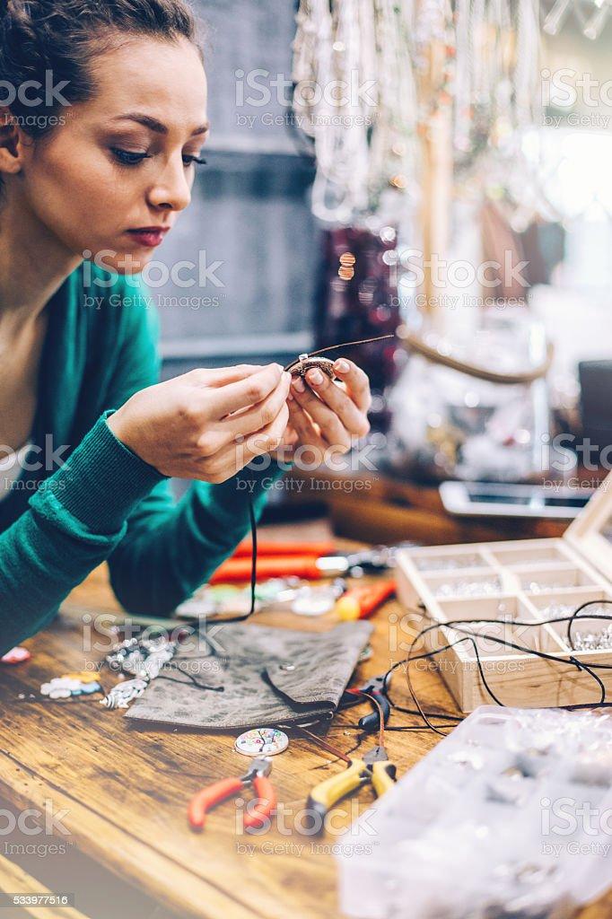 Young woman making handmade jewelry stock photo