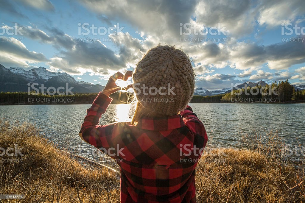 Young woman making heart shape frame with hands to sunset stock photo
