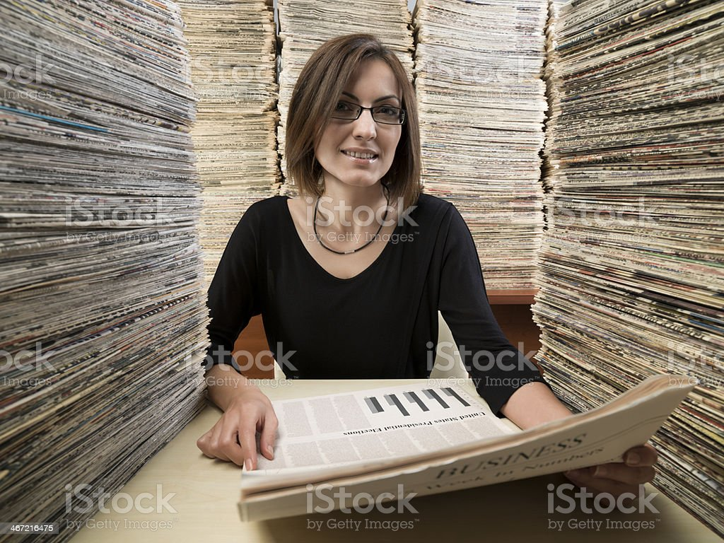 Young woman making research in archive of newspapers stock photo