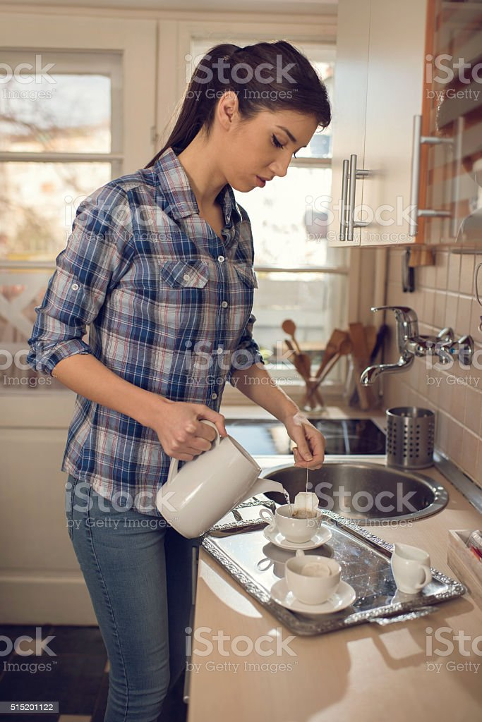 Young woman making tea in the kitchen. stock photo