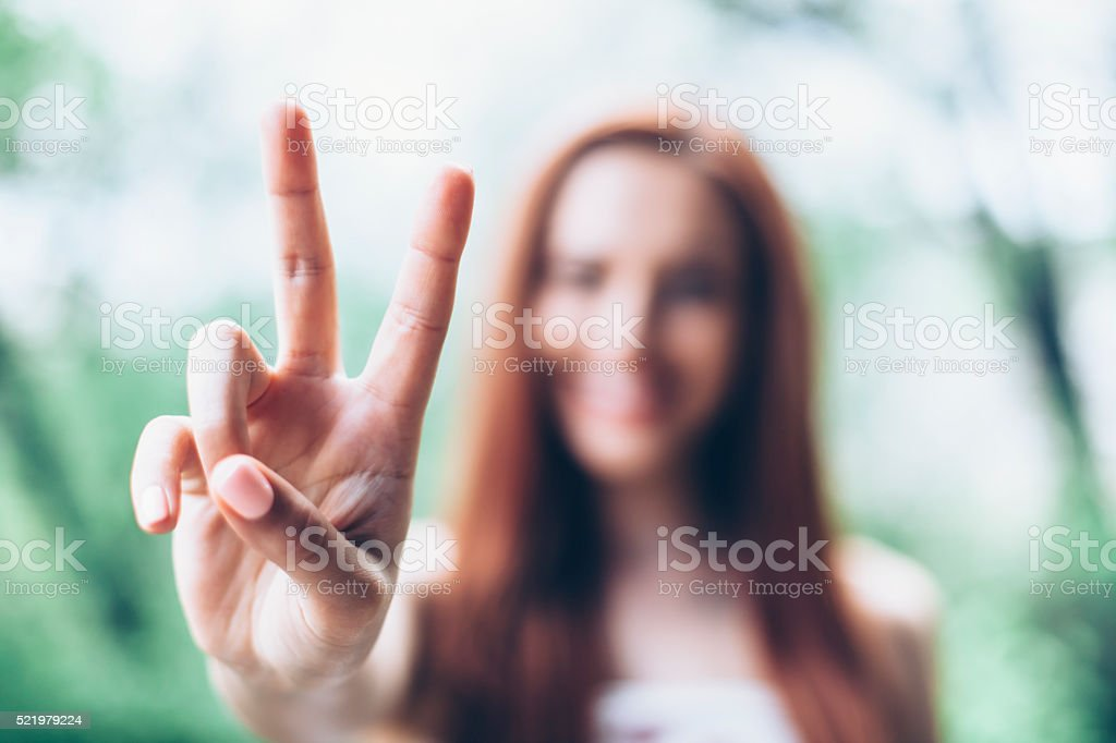 Young woman making victory sign stock photo