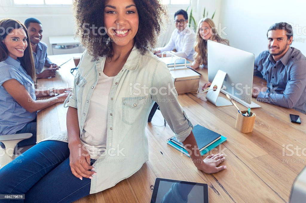 Young woman manager standing in front of her team. stock photo