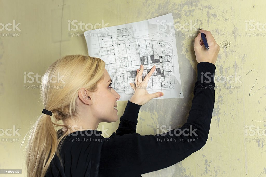Young woman marking the wall - home renovation royalty-free stock photo