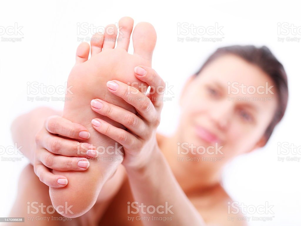 Young woman massages her foot royalty-free stock photo