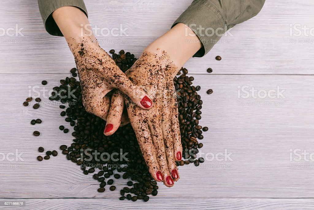 Young woman massaging a hand with coffee scrub stock photo