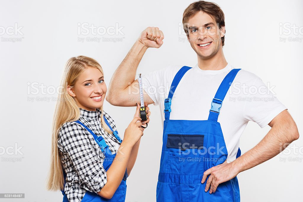 Young woman measuring repairman biceps stock photo