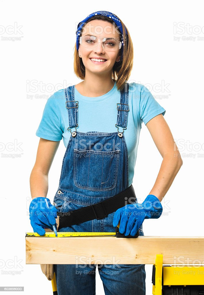 Young Woman Measuring Two by Four on White stock photo