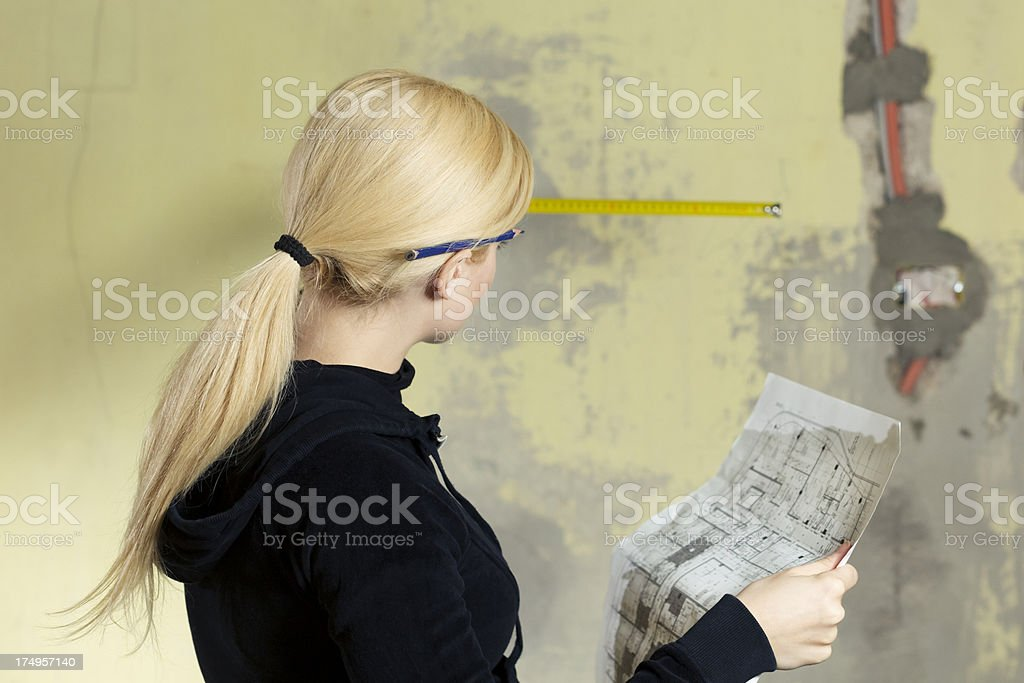 Young woman measuring wall - home renovation royalty-free stock photo