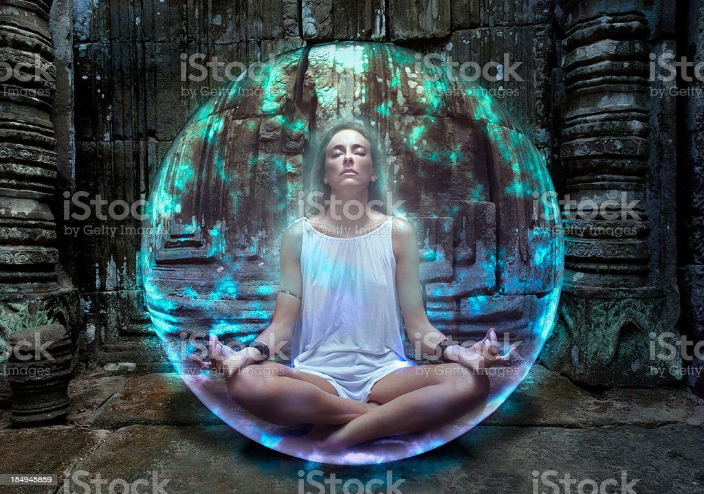 Young woman meditates inside protective bubble stock photo