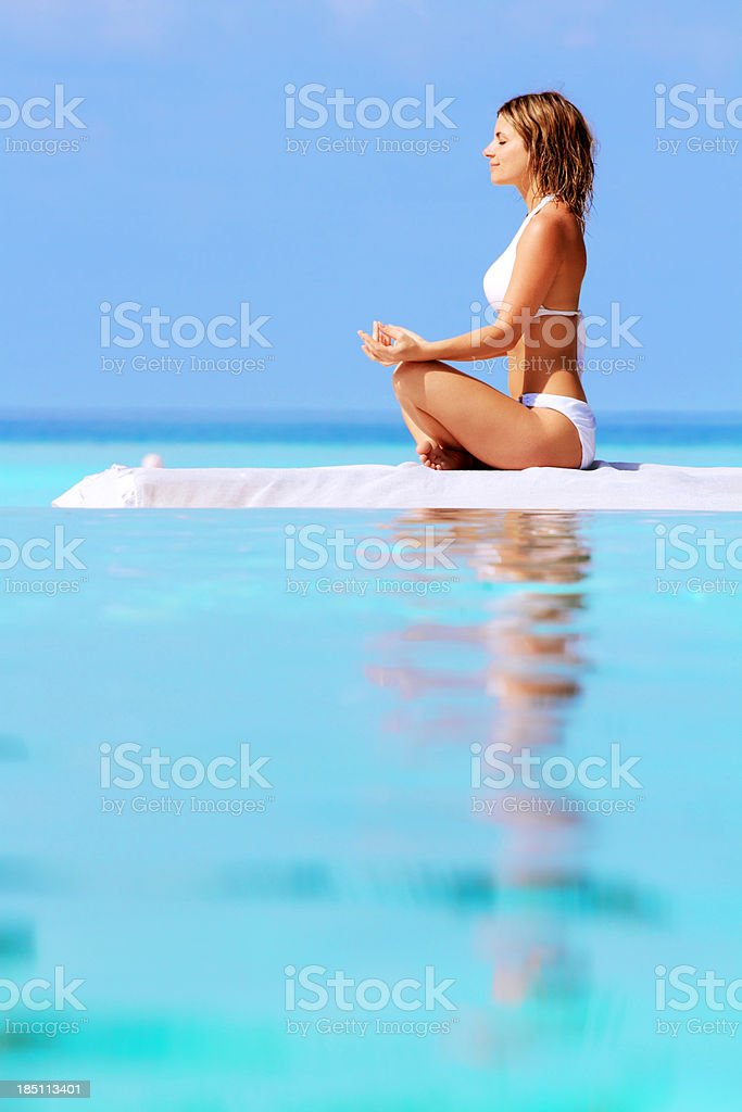 Young woman meditating against the blue sea. royalty-free stock photo