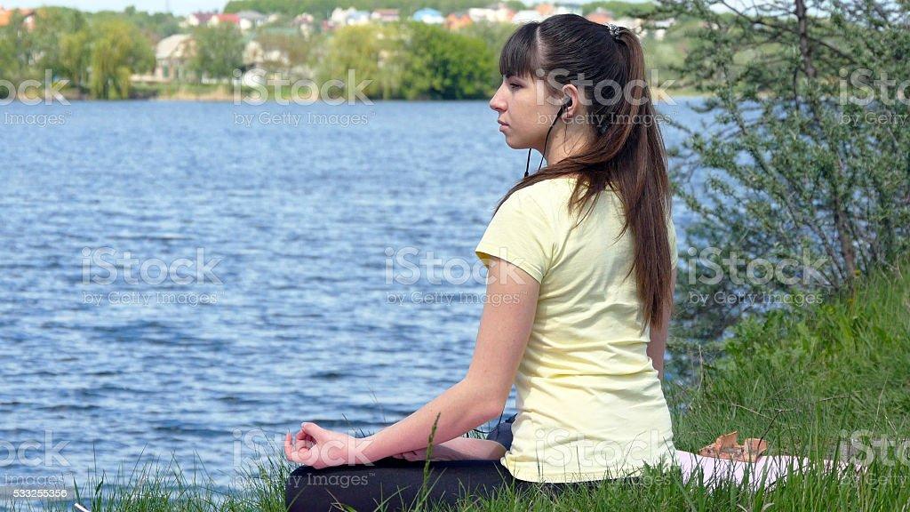 Mujer joven Meditando y escuchar música en teléfono inteligente en auriculares foto de stock libre de derechos