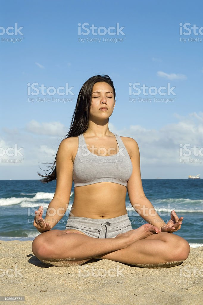 Young Woman Meditating and Practicing Yoga on the Beach royalty-free stock photo