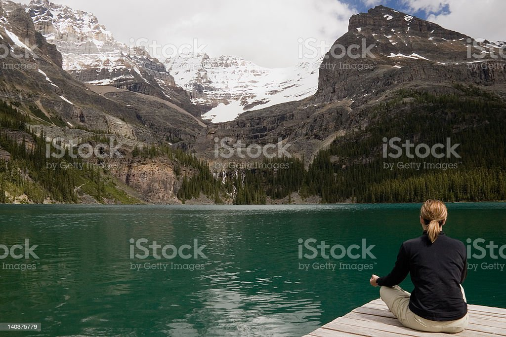 Young woman meditating beside a mountain lake royalty-free stock photo