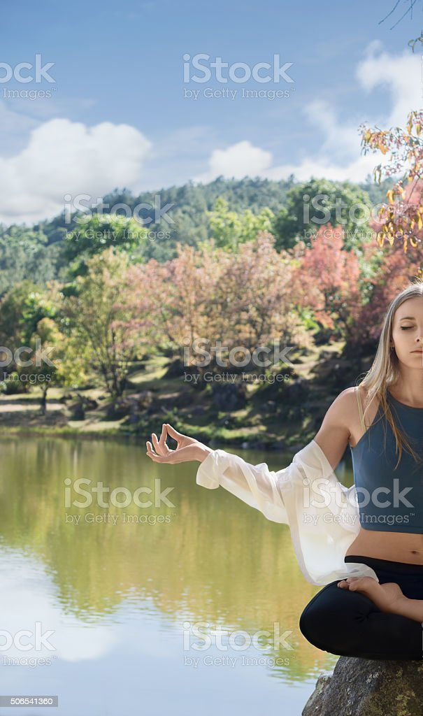 Young woman meditating by the water stock photo
