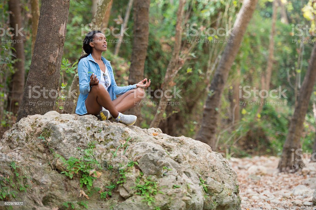 Young woman meditating in forest. stock photo