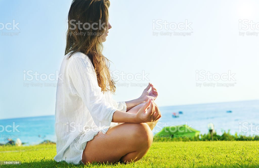 Young Woman Meditating in Lotus Position Outdoor stock photo