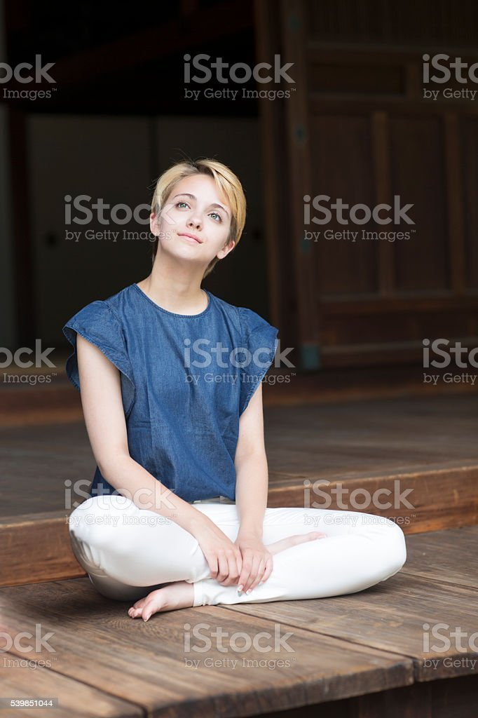 Young woman meditating in lotus position stock photo