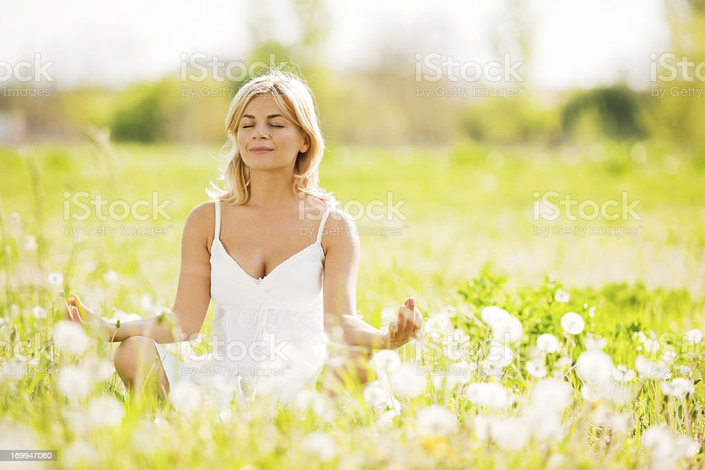 Young woman meditating in the mature. royalty-free stock photo