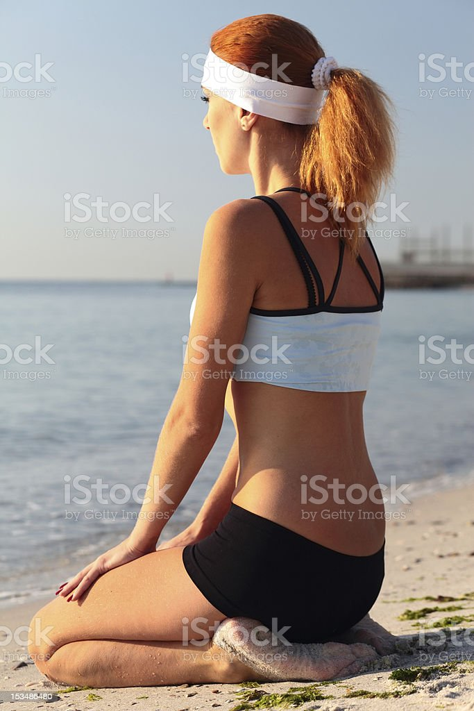 Young woman meditating on a beautiful beach. royalty-free stock photo