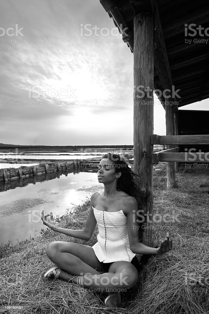 Young Woman Meditating on Shore in Evening royalty-free stock photo