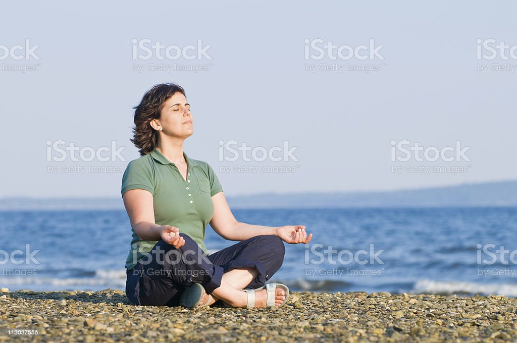 Young woman meditating on the beach royalty-free stock photo