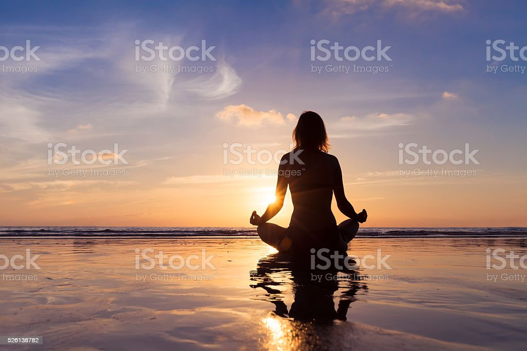 Young woman meditating on the beach with yoga at sunrise stock photo