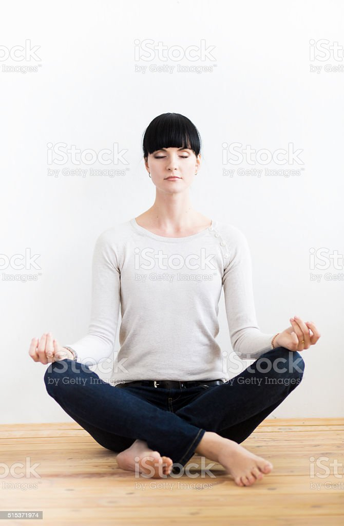 Young Woman Meditating On Wooden Floor In Office stock photo