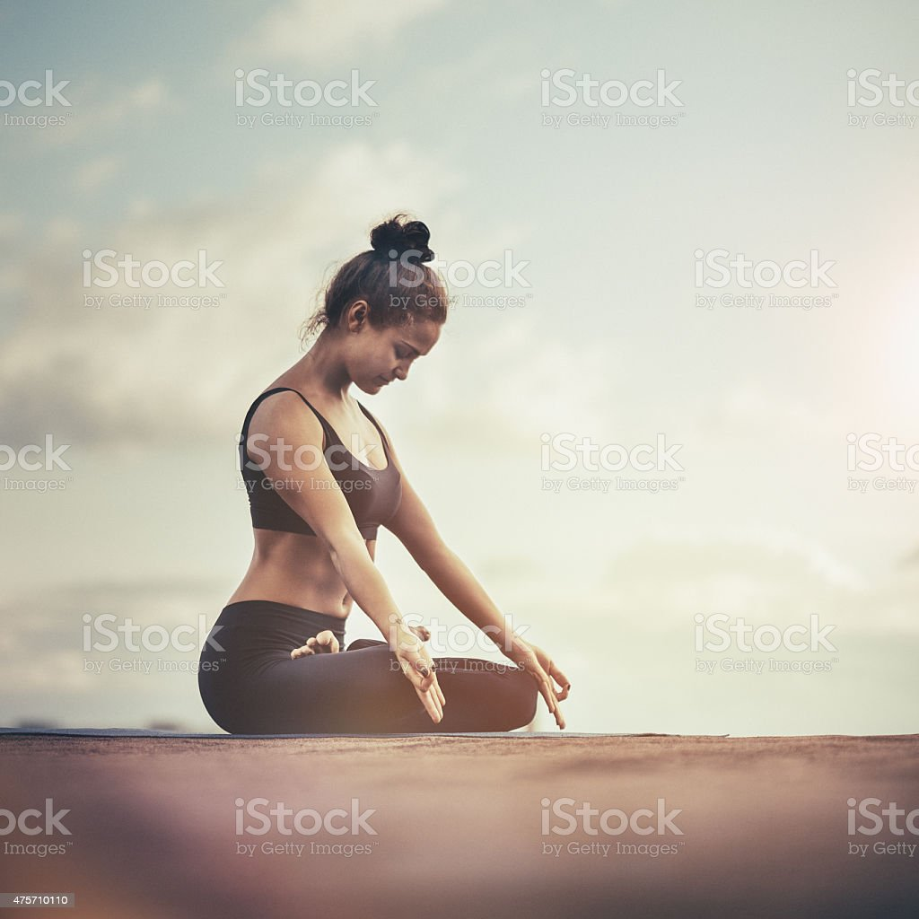 Young woman meditating outdoors on a rooftop at sunset stock photo