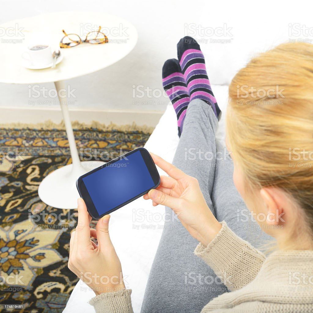 Young Woman Messaging W Smart Phone on Sofà stock photo