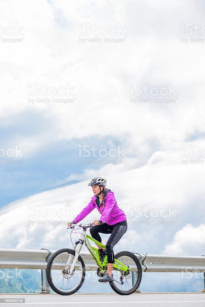 Young Woman Mountain Biking Uphill in the Swis Alps stock photo