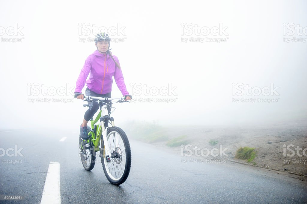 Young Woman Mountain Biking Uphill in the Swiss Alps stock photo