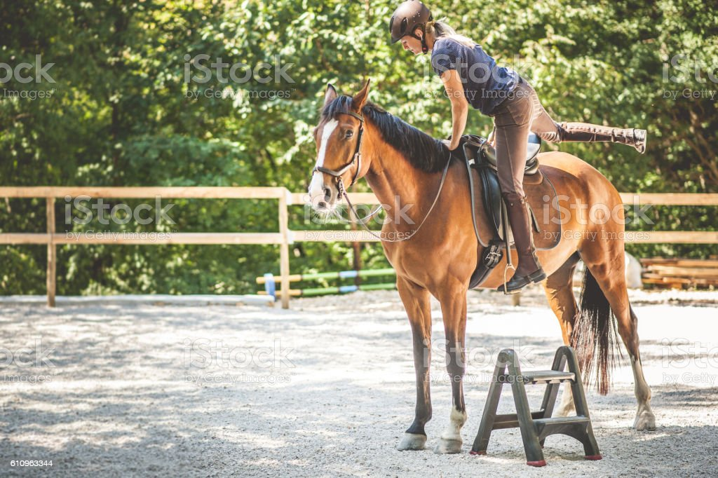 Young Woman Mounting a Horse stock photo