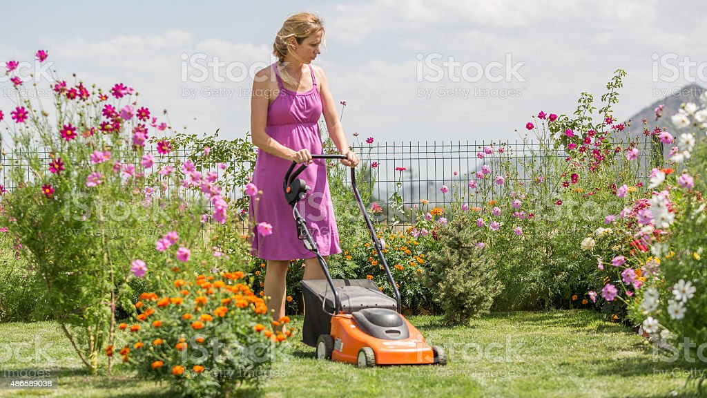 young woman mowing grass stock photo