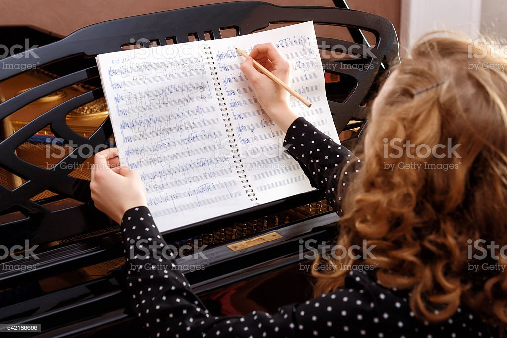 Young woman musician writes in music book pencil. stock photo