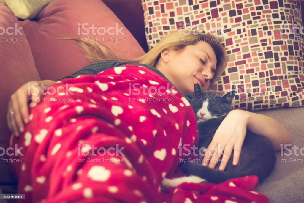 Young woman napping on the couch with her cat together stock photo