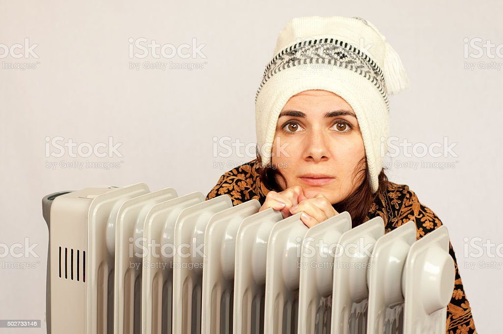 Young woman near a heater stock photo