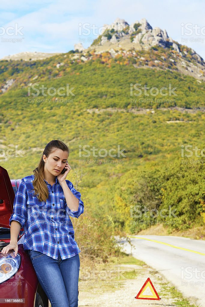 Young woman near broken car speaking by phone stock photo