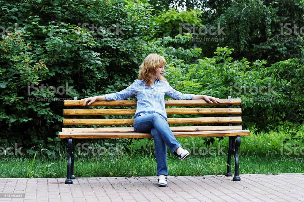 Young woman on a bench stock photo