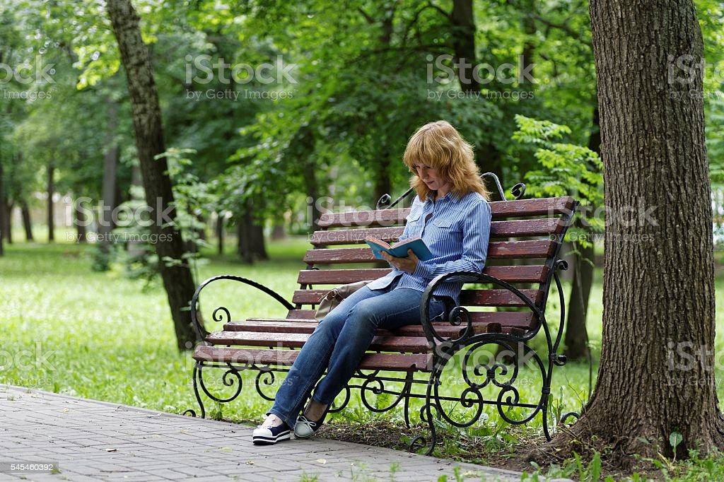 Young woman on a bench reading a book stock photo