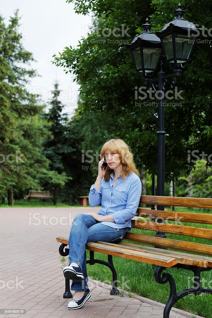 Young woman on a bench talking on the phone stock photo