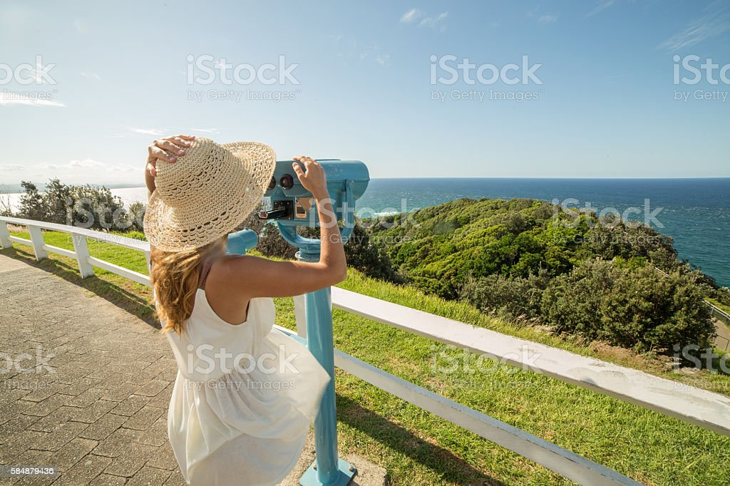 Young woman on a cliff looking trough viewfinder stock photo