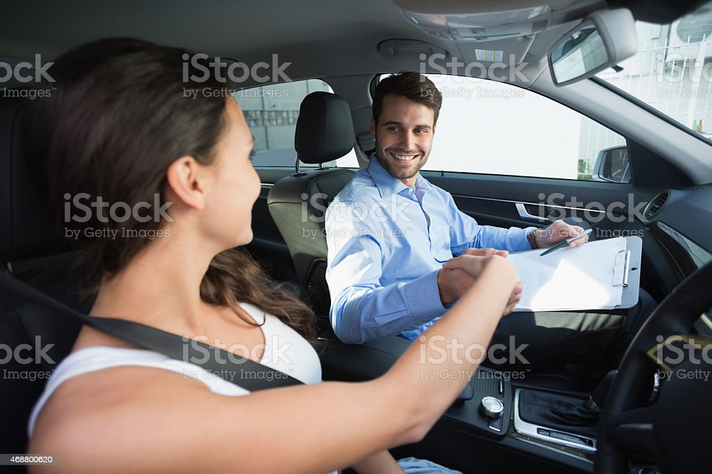 Young woman on a driving lesson from a young man stock photo
